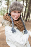 Woman in fur hat with woolen scarf and jacket in the woods Royalty Free Stock Photo