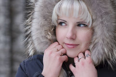 Woman with a fur hood. Portrait of the beautiful, smiling young woman with a fur hood Royalty Free Stock Images