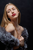 Woman in fur. Luxury woman in fur coat on black background Stock Images