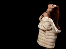Woman in fur. Luxury woman in fur coat showing big breast on black background with copyspace Royalty Free Stock Photos