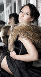 Woman with fur stole. Attractive glamorous woman in erotic pose with fur stole and lacy stocking top showing Royalty Free Stock Image