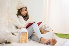 Woman with fur sweater relax during xmas. Beautiful attractive mole woman with white fur hat and sweater read book in bedroom at winter with copy space for text stock photography
