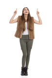 Woman In Fur Vest Looking Up And Pointing. Beautiful young woman in brown fur waistcoat, khaki pants and black boots is holding arms raised, looking up and Stock Images