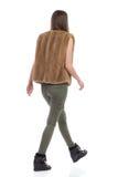 Woman In Fur Waistcoat Walking Rear View Stock Photo