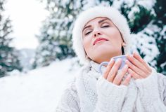 Woman in fur white hat enjoy with warm drink Royalty Free Stock Photography