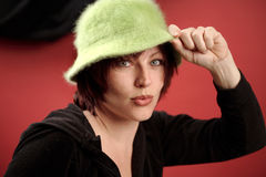 Woman in furry hat. A woman poses playfully, holding on to the brim of a furry green hat Stock Image