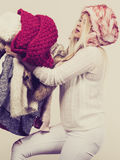 Woman in furry hat holding clothes pile Royalty Free Stock Photo