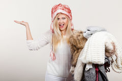 Woman in furry hat holding clothes pile Royalty Free Stock Image