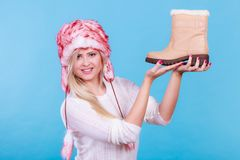 Woman in furry winter hat holding beige boots. Shoes for cold days ideas, fashion, clothes concept. Woman in furry winter hat holding warm, beige boots royalty free stock photos