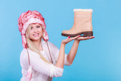 Woman in furry winter hat holding beige boots Stock Photography