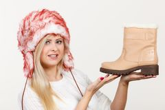 Woman in furry winter hat holding beige boots Royalty Free Stock Photos
