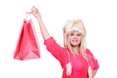 Woman in furry winter hat holding shopping bags. Clothing, seasonal sales and accessories concept. Woman in warm furry winter hat holding shopping bags Stock Photo