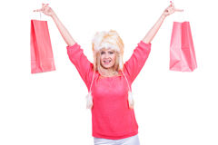 Woman in furry winter hat holding shopping bags. Clothing, seasonal sales and accessories concept. Woman in warm furry winter hat holding shopping bags Royalty Free Stock Image
