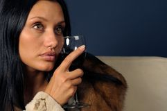 Woman in furs witn wine. Stock Photos