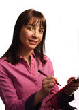 Woman in fushia shirt takes notes. Isolated over white Royalty Free Stock Photo