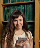 A woman with a gadget against the bookstand Royalty Free Stock Photography