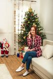 Woman with gadget at christmastime. Cheerful young woman talking on smartphone while sitting on sofa at christmastime royalty free stock photos