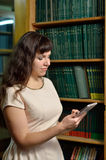 A woman with a gadget in the library Stock Photography
