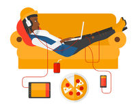 Woman with gadgets lying on sofa. An african-american woman in headphones lying on a sofa with electronic devices and fast food vector flat design illustration royalty free illustration