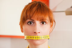 Woman gagged by a tape measure. Symbol for eating disorder royalty free stock image