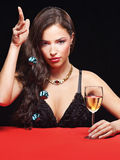 Woman gambling on red table. Pretty young woman holding dices on red table royalty free stock images