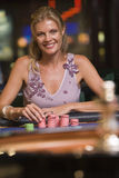 Woman gambling at roulette table. In casino Stock Photo
