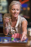 Woman gambling at roulette table Stock Images