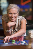 Woman gambling at roulette table. In casino royalty free stock photos
