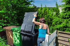 Woman at a garbage bin Stock Photo