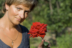 Woman in the garden. Portrait of a smiling woman with a dreamy red rose Royalty Free Stock Image