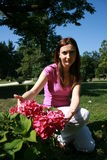 Woman in the garden. Woman crouching in the garden and showing disappointed a Hortensia in the garden Stock Photos