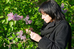 Woman in the garden. Middle aged woman smelling flowers in the park/garden Stock Photography