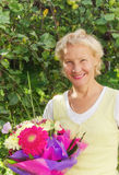 Woman in the garden with a bouquet of flowers Stock Photos