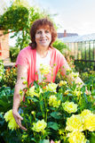 Woman in the garden cares for flowers Stock Photos