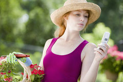 Woman in garden with cell phone. Pretty young woman gardener looking at her cell phone Stock Photos