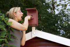 Woman in garden controls bird house Royalty Free Stock Photography