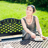 Woman in the garden. Woman drinking coffee in the garden Stock Images