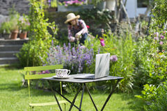 Woman in a garden, focus on cup of tea and laptop foreground Stock Photo