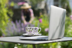 Woman in a garden, focus on cup of tea and laptop foreground Royalty Free Stock Image