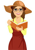 Woman with garden hat and glasses reading gardening journal Stock Image