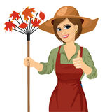Woman with garden hat holding rake. Gardening. Woman with garden hat holding rake and showing thumbs up isolated over white background royalty free illustration