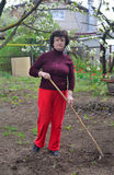 Woman in the garden with a hoe Stock Photography