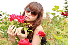 Woman in garden with roses Royalty Free Stock Photo