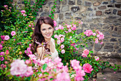 Woman in a garden of roses Stock Image