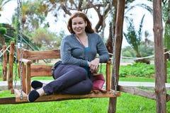Woman on the garden swing Stock Photo