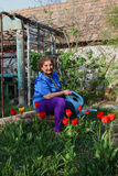 Woman in garden with watering can Royalty Free Stock Image