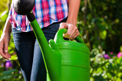 Woman in garden with watering can in hand Stock Photography