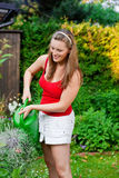 Woman in garden watering flowers Stock Photo