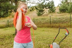 Woman rolling mower cable in garden. Woman after garden work rolling up on her arm orange wire cable mower equipment stock photos