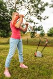Woman rolling mower cable in garden. Woman after garden work rolling up on her arm orange wire cable mower equipment royalty free stock photography
